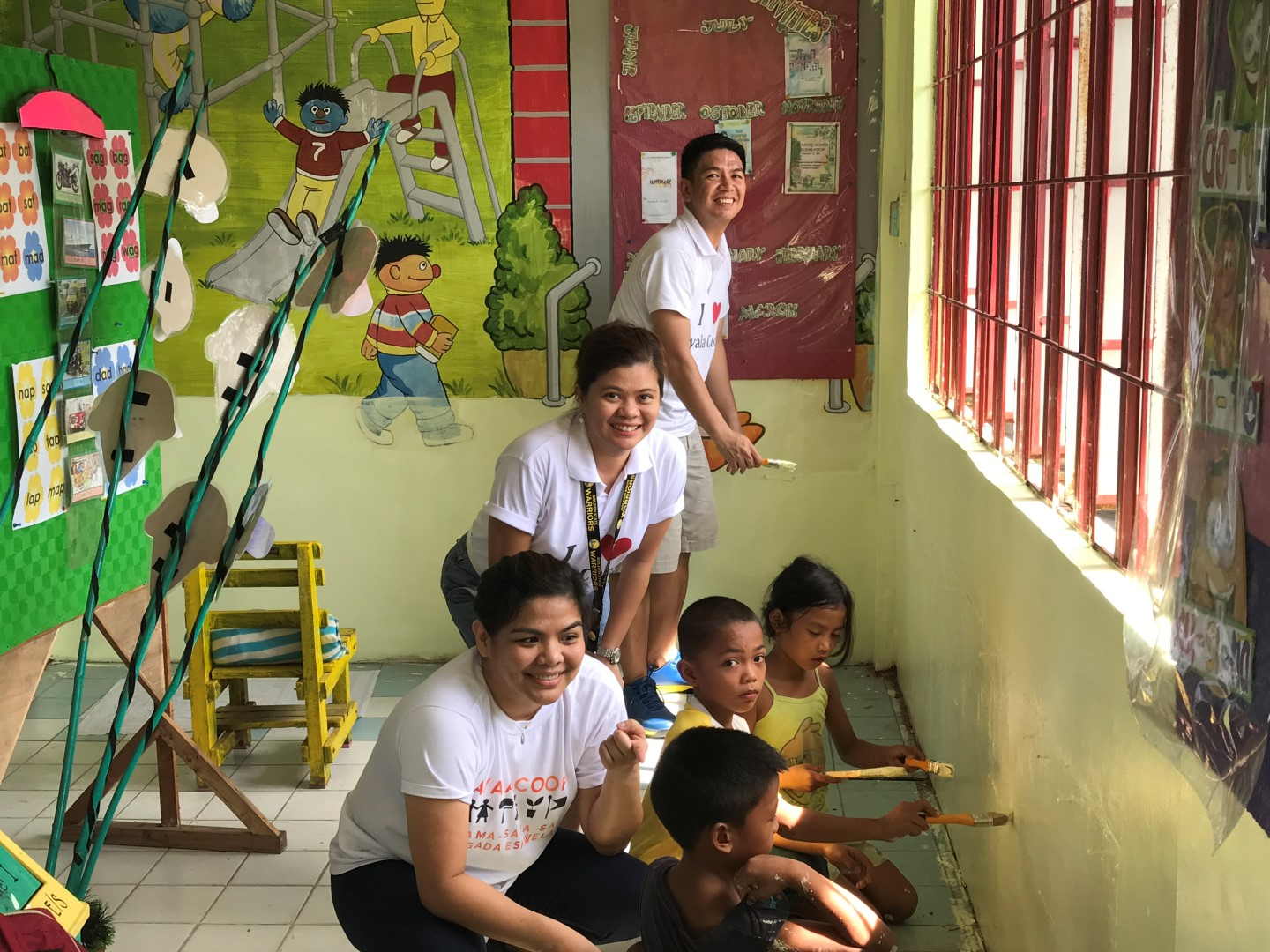 A Coop team led by Jenny Cura joins a group of pupils in painting the walls of their school as part of the Brigada Eskwela project.