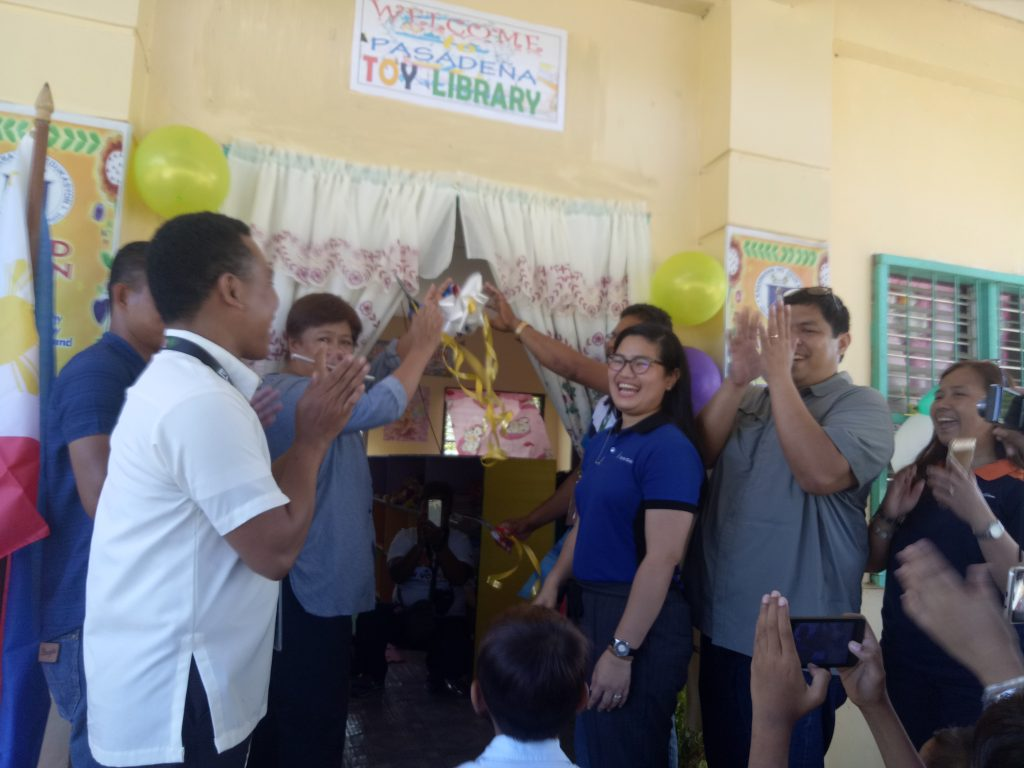 El Nido Vice Mayor Leonor Corral (third from left) and Department of Education District Supervisor Daniel Belleza (partly covered) cut the ceremonial ribbon opening the Pasadena Elementary School toy library in El Nido, Palawan as (from left, foreground) Pasadena head teacher Marlon Batoy, Lamoro Barangay Captain Dario Campuid, the Ayala Coop's Sarah Razonable, and the Philippine Toy Library's Edsel Ramirez and Chiara Cruz applaud.