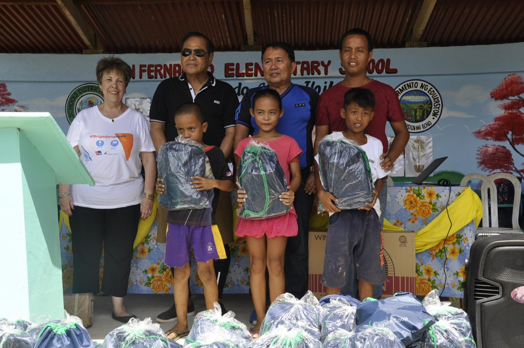 Three of the almost 200 children at the San Fernando Elementary School in Sicogon Island who received their school kits are shown with Ayala Coop General Manager Dina Orosa (left), Sicogon Mayor Betita (in shades) and San Fernando Elementary School principal Joerie Mangasang (right).