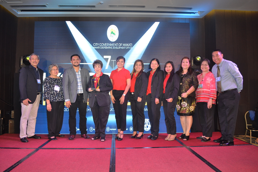 The Ayala Coop team is shown after receiving the trophy for best-performing coop in terms of total assets. Leading the Coop team is General Manager Dina Orosa (with trophy) as Makati Cooperative Development Office OIC Vivian Gabriel (third from right), Atty. Frederick Joe Robles of the Cooperative Development Authority (to Ms. Orosa's right) and other officials flank the Coop team members.